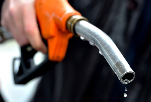 A man finishes to fill up at a gas stati